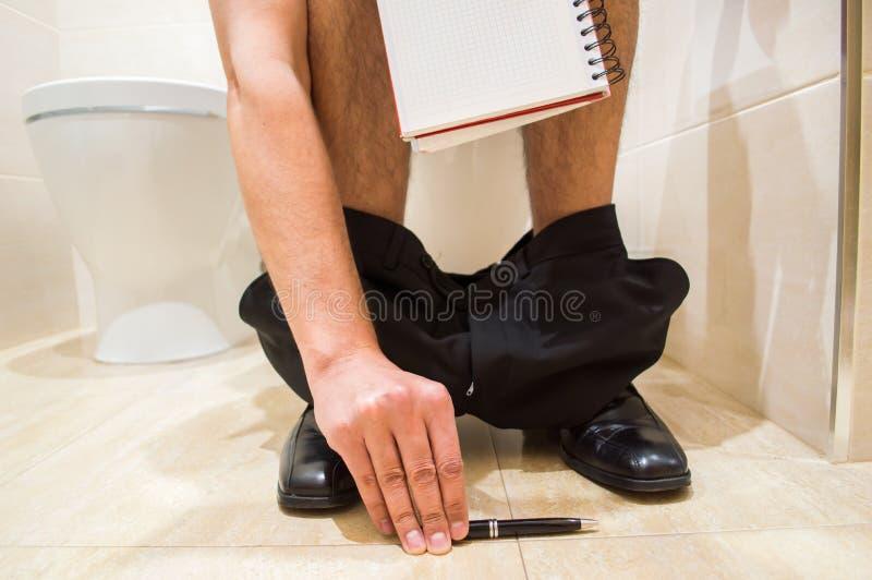 Επιχειρησιακό άτομο που εργάζεται στο WC στοκ φωτογραφία