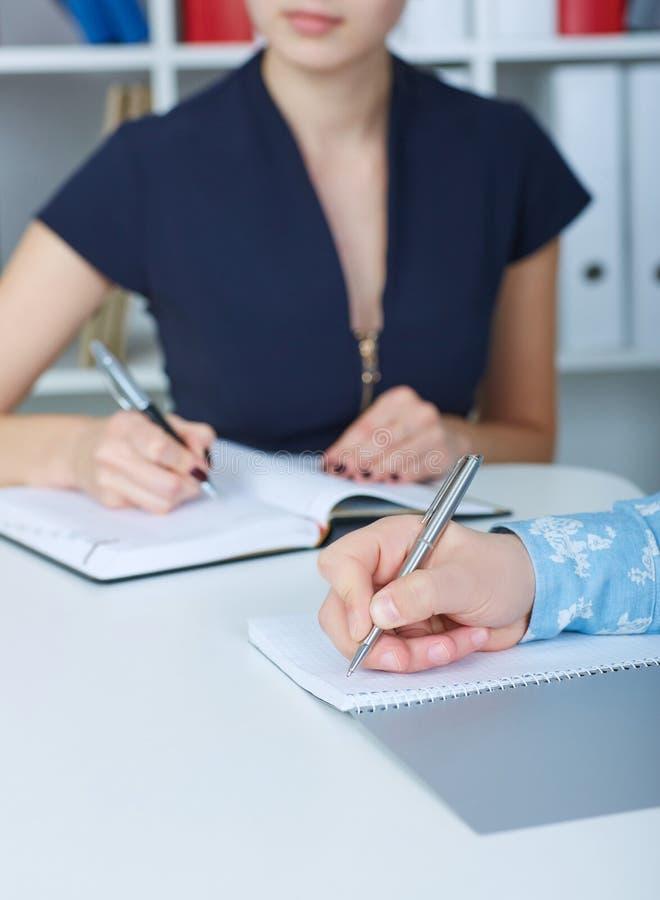 Επιχειρησιακό άτομο που κάνει τις σημειώσεις στον εργασιακό χώρο γραφείων με τη γυναίκα συνάδελφός του στο υπόβαθρο Προσφορά επιχ στοκ εικόνα με δικαίωμα ελεύθερης χρήσης