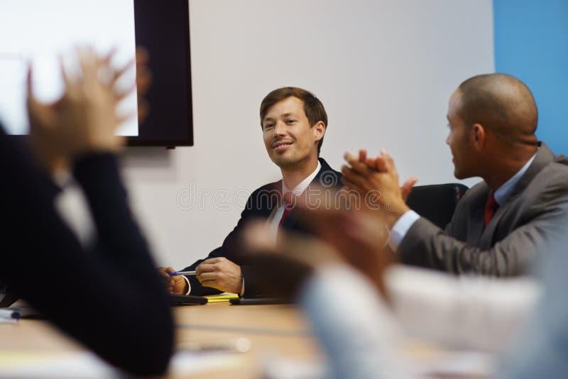 Επιχειρησιακό άτομο που κάνουν την παρουσίαση και άνθρωποι που επιδοκιμάζουν στη συνεδρίαση στοκ εικόνες