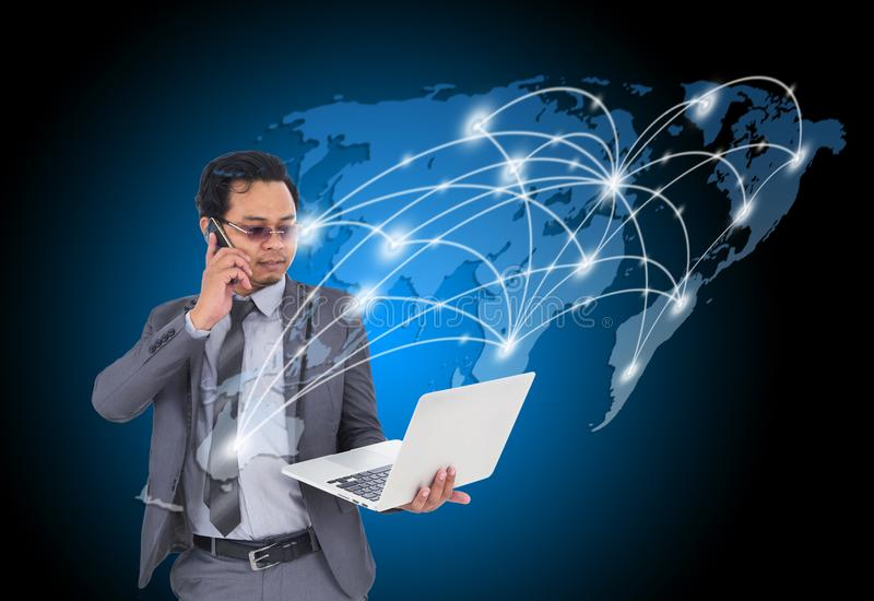Επιχειρησιακό άτομο που μιλά στο κινητό τηλέφωνο και που χρησιμοποιεί το lap-top με τον κόσμο στοκ εικόνες