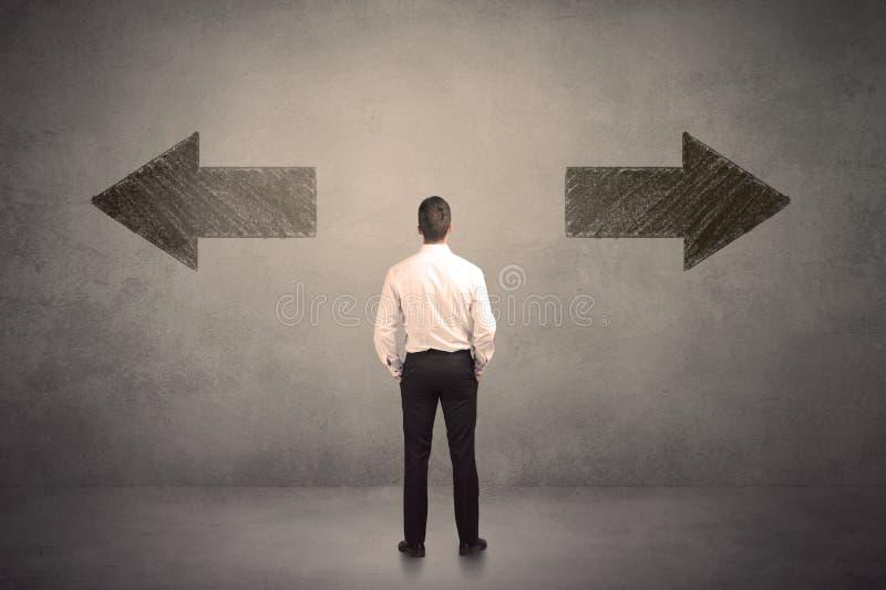 Επιχειρησιακό άτομο που παίρνει μια απόφαση στεμένος μπροστά από δύο βρώμικα βέλη στον τοίχο στοκ φωτογραφίες