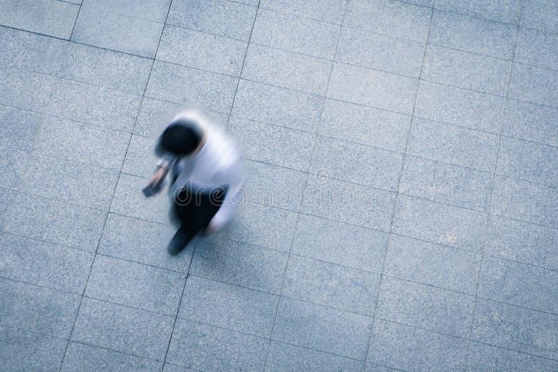 Επιχειρησιακό άτομο που περπατά και που χρησιμοποιεί το έξυπνο τηλέφωνο στοκ φωτογραφίες