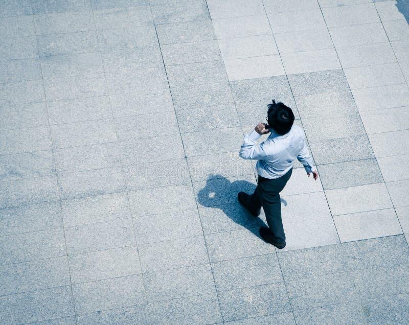 Επιχειρησιακό άτομο που περπατά και που χρησιμοποιεί το έξυπνο τηλέφωνο στοκ εικόνες