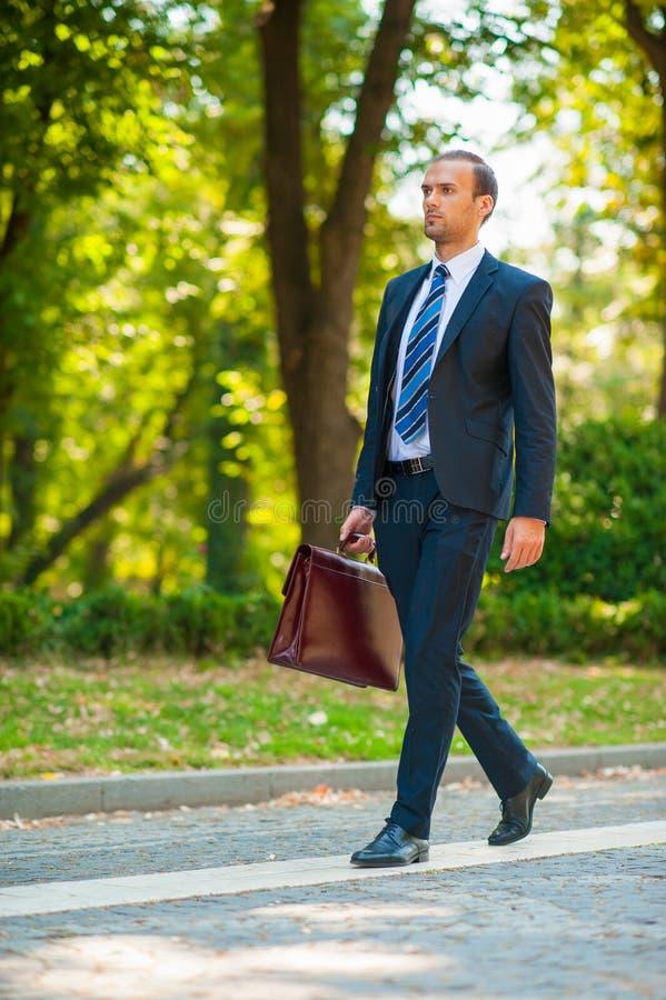 Επιχειρησιακό άτομο που περπατά στο πάρκο στοκ φωτογραφία