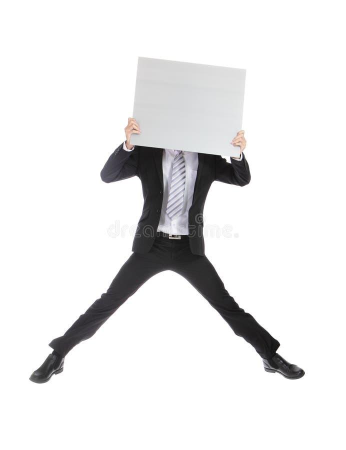 Επιχειρησιακό άτομο που πηδά και που κρατά τον πίνακα διαφημίσεων στοκ εικόνα