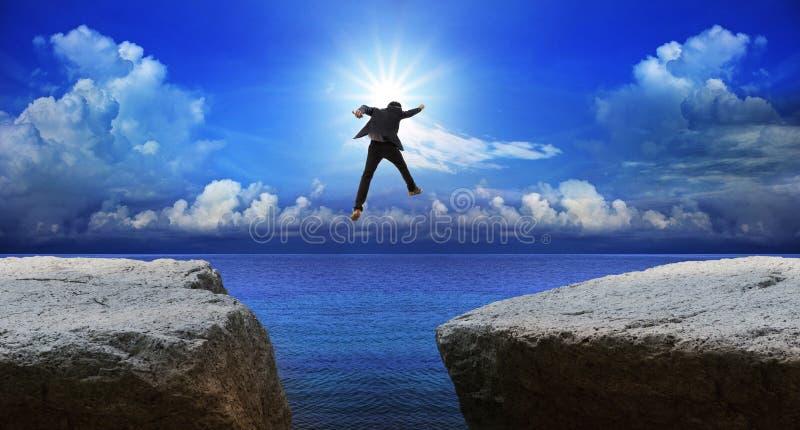 Επιχειρησιακό άτομο που πηδά στον επόμενο απότομο βράχο με την απόφαση κινδύνου στοκ φωτογραφίες με δικαίωμα ελεύθερης χρήσης