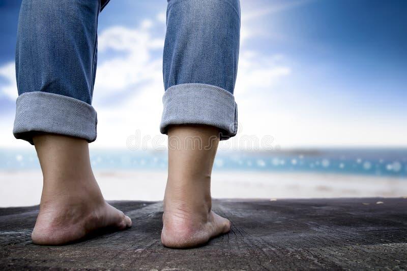 Επιχειρησιακό άτομο που στέκεται στο ξύλινο υπόβαθρο πατωμάτων και παραλίας στοκ εικόνες
