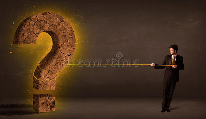 Επιχειρησιακό άτομο που τραβά μια μεγάλη στερεά πέτρα ερωτηματικών στοκ εικόνα με δικαίωμα ελεύθερης χρήσης