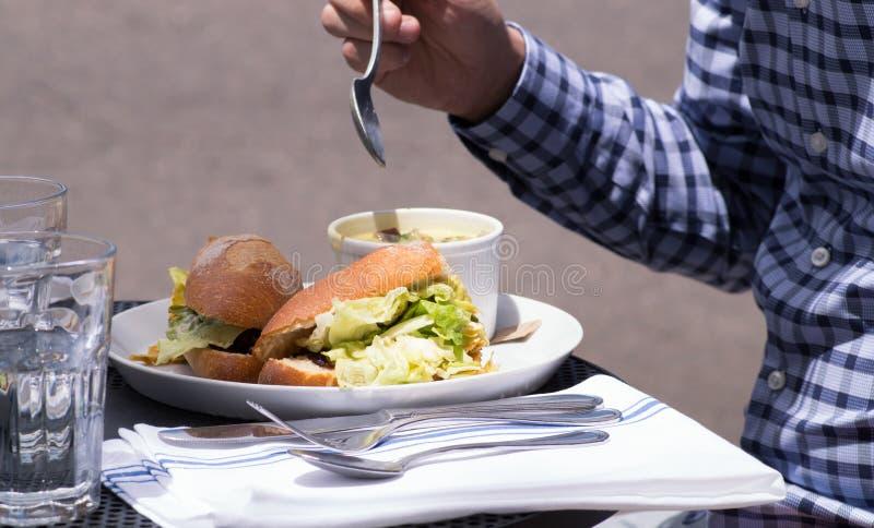 Επιχειρησιακό άτομο που τρώει το μεσημεριανό γεύμα, που εξυπηρετείται στο θερινό πεζούλι του εστιατορίου στοκ φωτογραφία