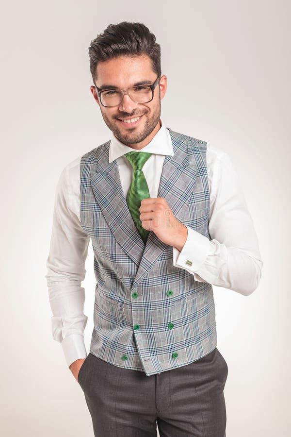 Επιχειρησιακό άτομο που φορά το άσπρο πουκάμισο, την γκρίζα φανέλλα και τον πράσινο δεσμό στοκ εικόνες