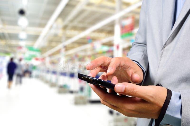 Επιχειρησιακό άτομο που χρησιμοποιεί το κινητό τηλέφωνο ψωνίζοντας στην υπεραγορά στοκ εικόνα
