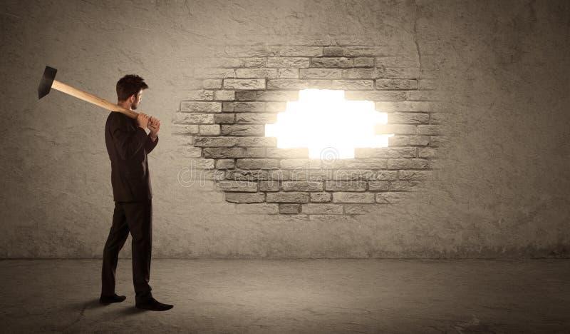 Επιχειρησιακό άτομο που χτυπά το τουβλότοιχο με το σφυρί και που ανοίγει μια τρύπα στοκ εικόνες