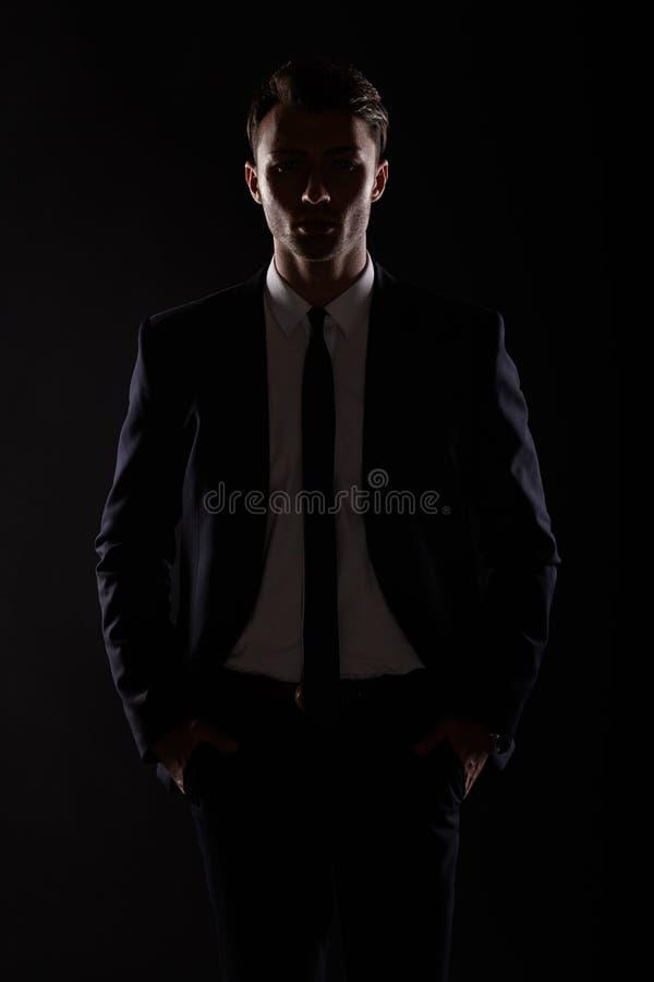 Επιχειρησιακό άτομο στη μαύρη ακολουθία, backlight στοκ φωτογραφία