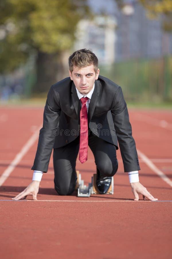 Επιχειρησιακό άτομο στο κοστούμι που αρχίζει και που προετοιμάζεται να τρέχει στην τρέχοντας διαδρομή απόδοσης ανταγωνισμού στοκ εικόνα