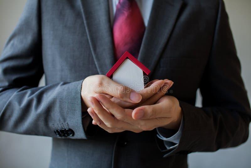 Επιχειρησιακό άτομο στο κοστούμι που χρησιμοποιεί τα χέρια που καλύπτουν και που προστατεύουν το σπίτι στοκ φωτογραφίες