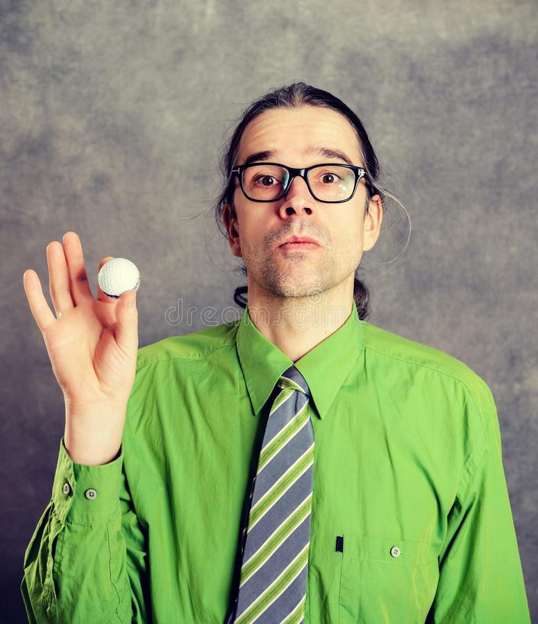 Επιχειρησιακό άτομο στο πράσινο πουκάμισο και γραβάτα με τη σφαίρα γκολφ στοκ εικόνες