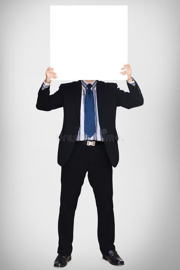 Επιχειρησιακό άτομο στο σκοτεινό κοστούμι που κρατά ένα κενό σημάδι στοκ εικόνες