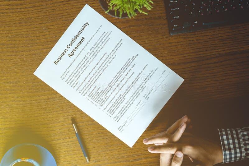 Επιχειρησιακό έγγραφο συμφωνίας συνεργασίας που υπογράφεται από ένα πρόσωπο στον πίνακα στο γραφείο στοκ εικόνες