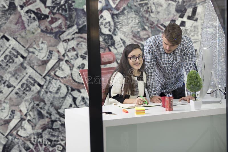 Επιχειρησιακό ζεύγος που εργάζεται μαζί στο πρόγραμμα στο σύγχρονο γραφείο ξεκινήματος στοκ εικόνα
