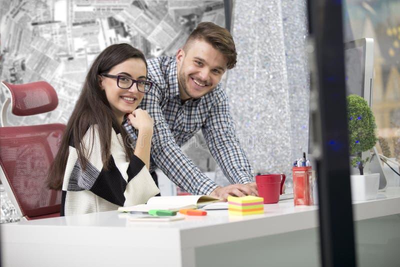 Επιχειρησιακό ζεύγος που εργάζεται μαζί στο πρόγραμμα στο σύγχρονο γραφείο ξεκινήματος στοκ εικόνες