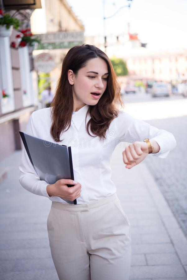 Επιχειρησιακό κορίτσι σε μια βιασύνη που εξετάζει το ρολόι της στοκ φωτογραφία