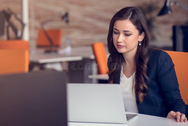 Επιχειρησιακό μήνυμα δακτυλογράφησης Βέβαια νέα γυναίκα στην έξυπνη περιστασιακή ένδυση που κρατά το έξυπνο τηλέφωνο και που εξετ στοκ φωτογραφίες
