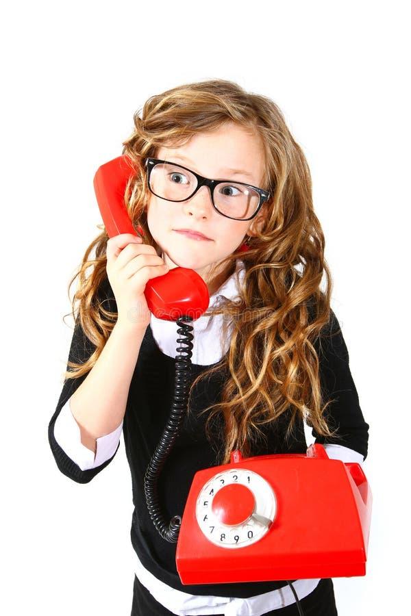 Επιχειρησιακό μικρό κορίτσι με ένα κόκκινο τηλέφωνο σε ένα άσπρο υπόβαθρο στοκ εικόνες