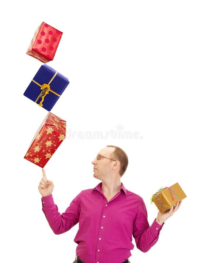 Επιχειρησιακό πρόσωπο που ισορροπεί τρία δώρα στοκ εικόνες