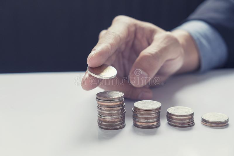 Επιχειρησιακό χέρι που βάζει την αυξανόμενη επιχείρηση σωρών νομισμάτων χρημάτων στοκ εικόνα