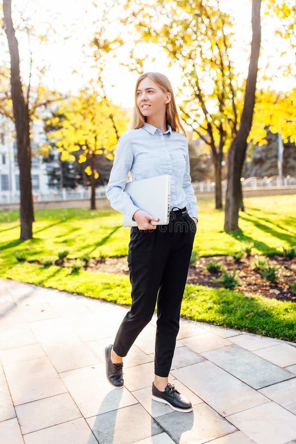 Επιχειρησιακό όμορφο κορίτσι που περπατά στο πάρκο με ένα lap-top στο ηλιοβασίλεμα στοκ φωτογραφίες με δικαίωμα ελεύθερης χρήσης