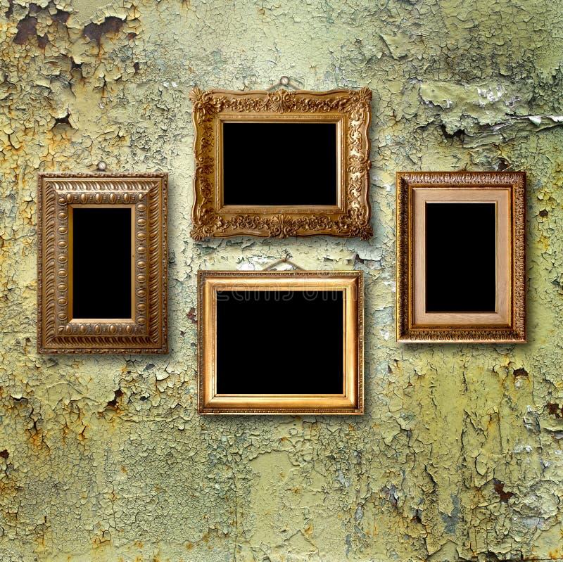 Επιχρυσωμένα ξύλινα πλαίσια για τις εικόνες στο σκουριασμένο μεταλλικό τοίχο στοκ εικόνα