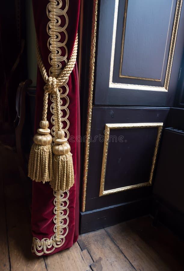 Επιχρυσωμένο σχοινί κουρτινών που συγκρατεί την κόκκινη κουρτίνα βελούδου στοκ εικόνα