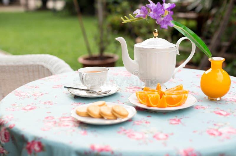 Επιλεγμένο αγγλικό τσάι φλυτζανιών τσαγιού εστίασης με τα πορτοκαλιά φρούτα και το μπισκότο στοκ εικόνες