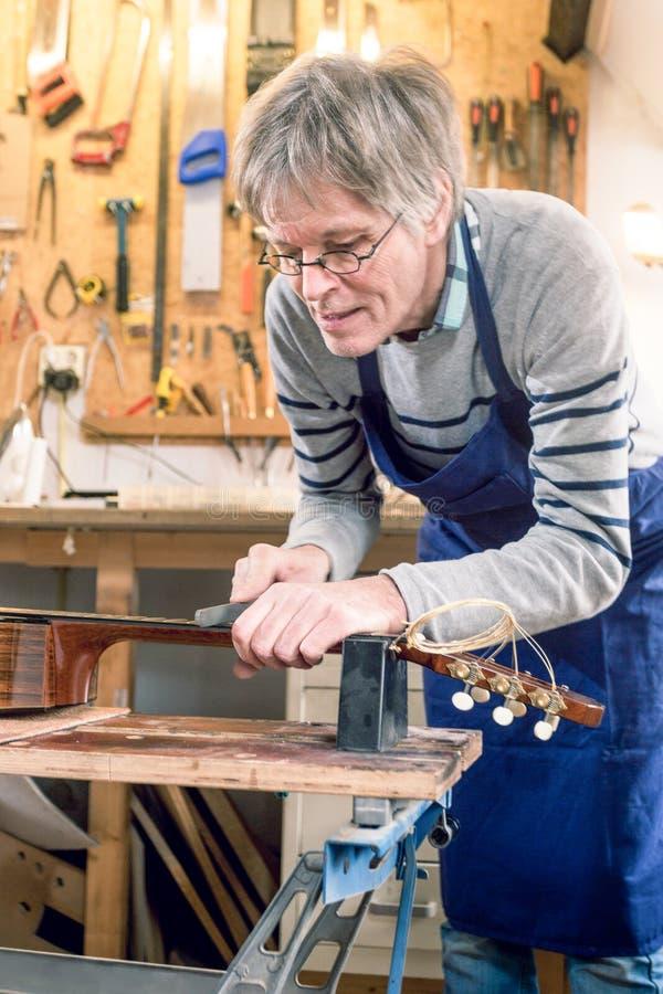 Επιδιορθωτής κιθάρων που αρχειοθετεί τους μαιάνδρους μιας ακουστικής κιθάρας στοκ εικόνα