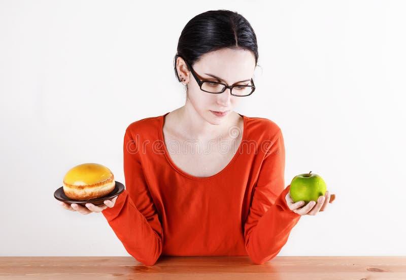 Επιλογή μεταξύ doughnut και του μήλου στοκ φωτογραφία