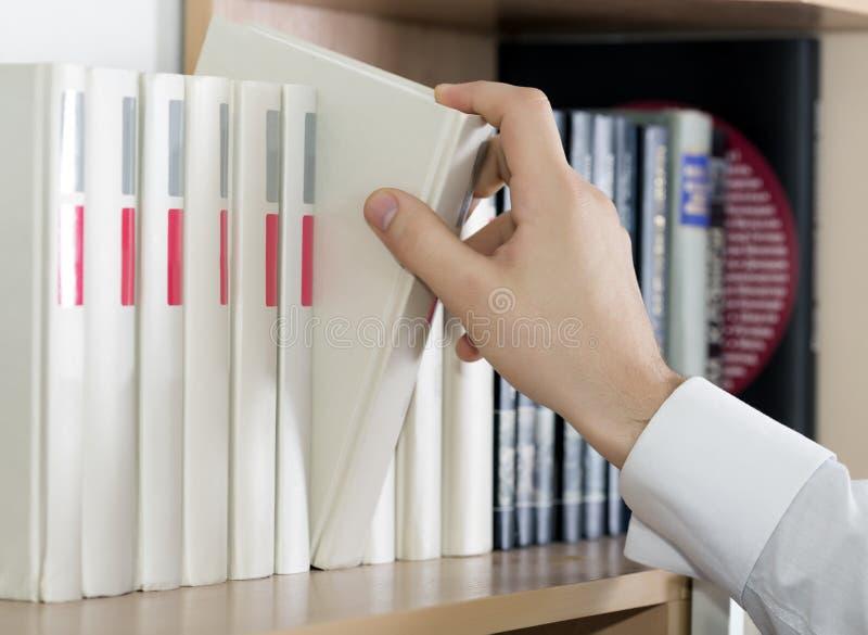 Επιλογή του χεριού βιβλίων του ατόμου στην άσπρη μανσέτα μανικιών στοκ φωτογραφίες με δικαίωμα ελεύθερης χρήσης