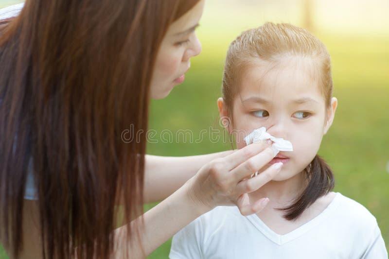 Εποχή γρίπης, φυσώντας μύτη μικρών κοριτσιών στοκ εικόνα