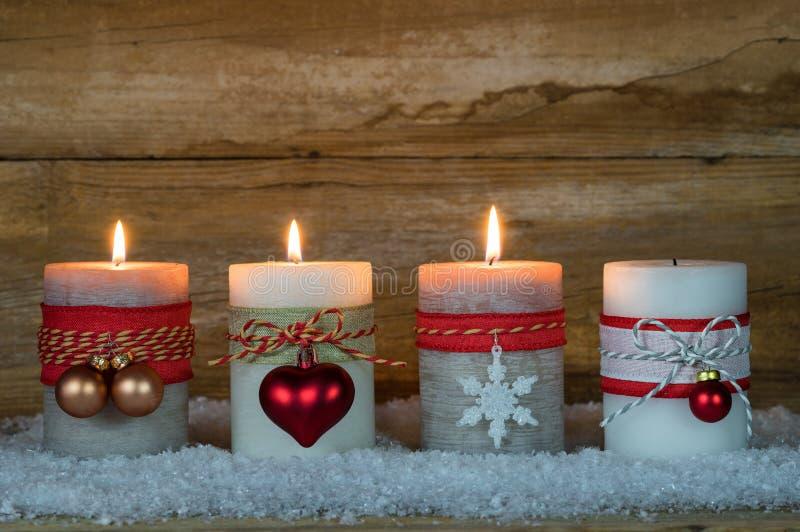 Εποχή εμφάνισης, τρία καίγοντας κεριά στο χιόνι στοκ εικόνες με δικαίωμα ελεύθερης χρήσης