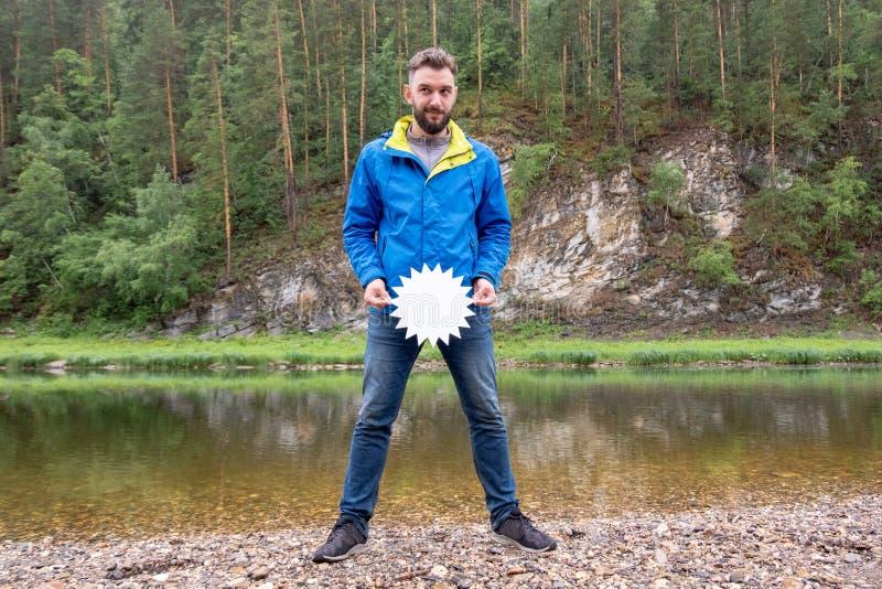 Εποχή των εκπτώσεων για τα ενδύματα φθινοπώρου για το ταξίδι Ένας αστείος τύπος τουριστών με μια γενειάδα κοιτάζει slyly στην πλε στοκ φωτογραφία με δικαίωμα ελεύθερης χρήσης