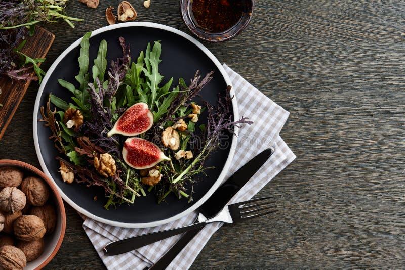 Εποχιακή σαλάτα με τα σύκα, τα ξύλα καρυδιάς και τα φρέσκα πράσινα στο ξύλινο υπόβαθρο στοκ εικόνες