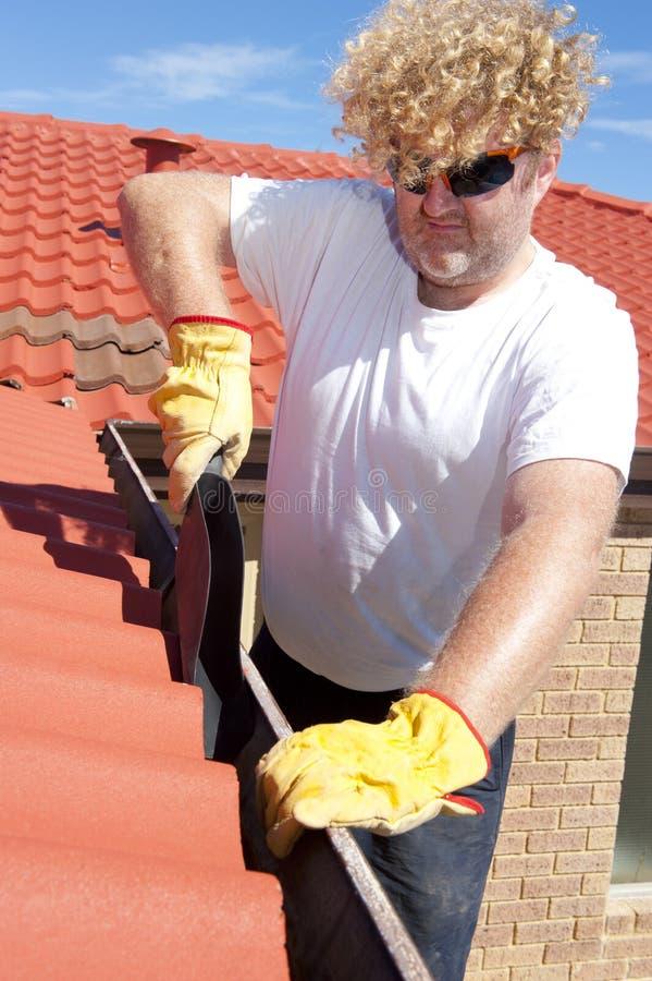 Εποχιακή υδρορροή ατόμων που καθαρίζει την κόκκινη στέγη στοκ εικόνες