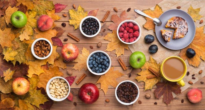 Εποχιακό υπόβαθρο φθινοπώρου Πλαίσιο των φύλλων σφενδάμου και ενός κέικ, των μούρων, των σταφίδων, των μήλων, των φρούτων, του κα στοκ φωτογραφία με δικαίωμα ελεύθερης χρήσης