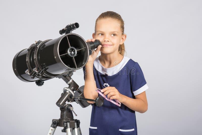 Επταετές κορίτσι που στέκεται δίπλα στο τηλεσκόπιο και τα βλέμματα ανακλαστήρων μυστιριωδώς στον ουρανό στοκ εικόνα