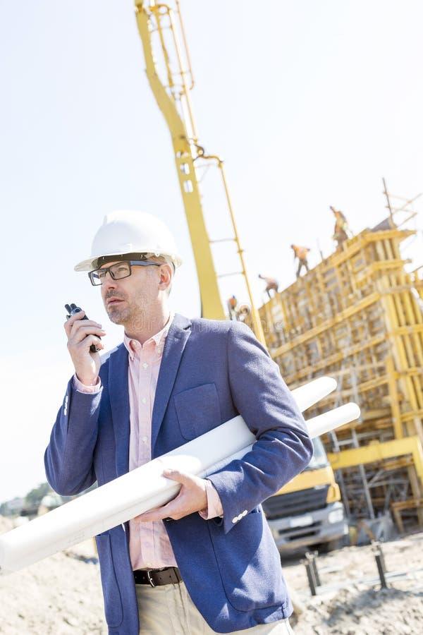 Επόπτης που χρησιμοποιεί walkie-talkie κρατώντας τα σχεδιαγράμματα στο εργοτάξιο οικοδομής στοκ εικόνα με δικαίωμα ελεύθερης χρήσης