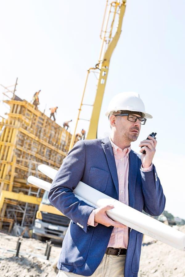 Επόπτης που χρησιμοποιεί walkie-talkie κρατώντας τα σχεδιαγράμματα στο εργοτάξιο οικοδομής στοκ εικόνες
