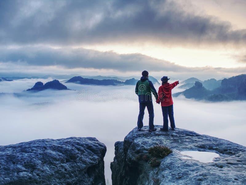 Εραστές που κατοπτρίζουν στο μάτι του νερού σε κορυφή βουνών πάνω από ομίχλη στοκ εικόνες