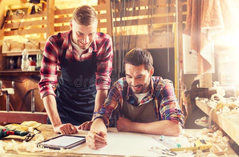 Εργάτες με το PC ταμπλετών και το σχεδιάγραμμα στο εργαστήριο στοκ εικόνες
