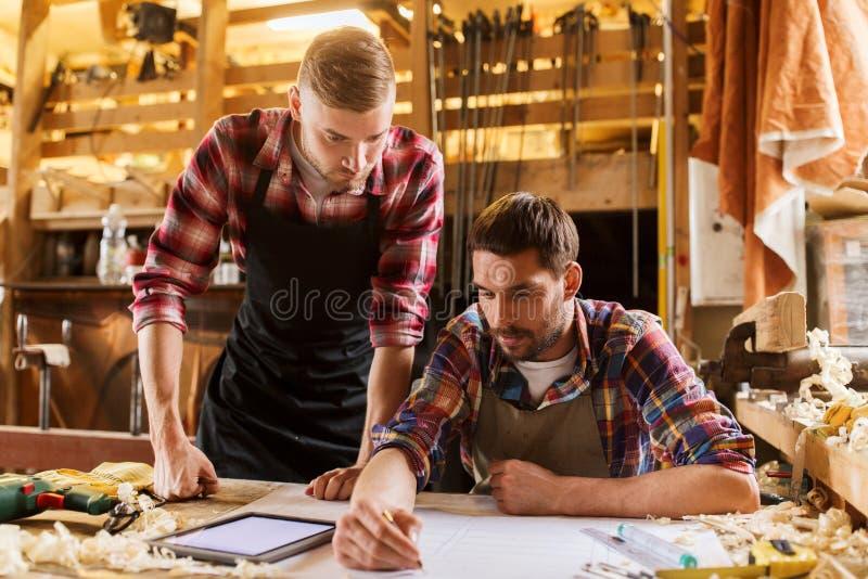 Εργάτες με το PC ταμπλετών και το σχεδιάγραμμα στο εργαστήριο στοκ φωτογραφίες με δικαίωμα ελεύθερης χρήσης