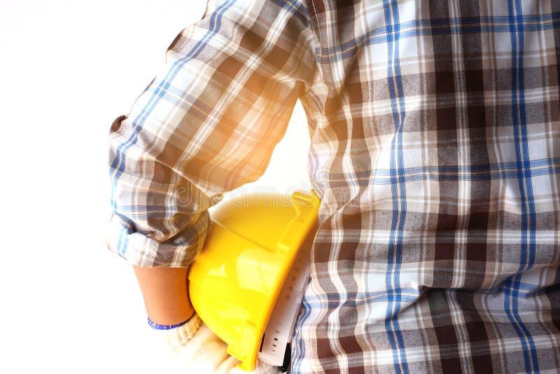 Εργάτες οικοδομών που κρατούν τα κίτρινα καπέλα ασφάλειας, άσπρο υπόβαθρο στοκ εικόνα