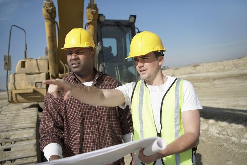 Εργάτες οικοδομών που εξετάζουν το σχέδιο για την περιοχή στοκ φωτογραφία με δικαίωμα ελεύθερης χρήσης